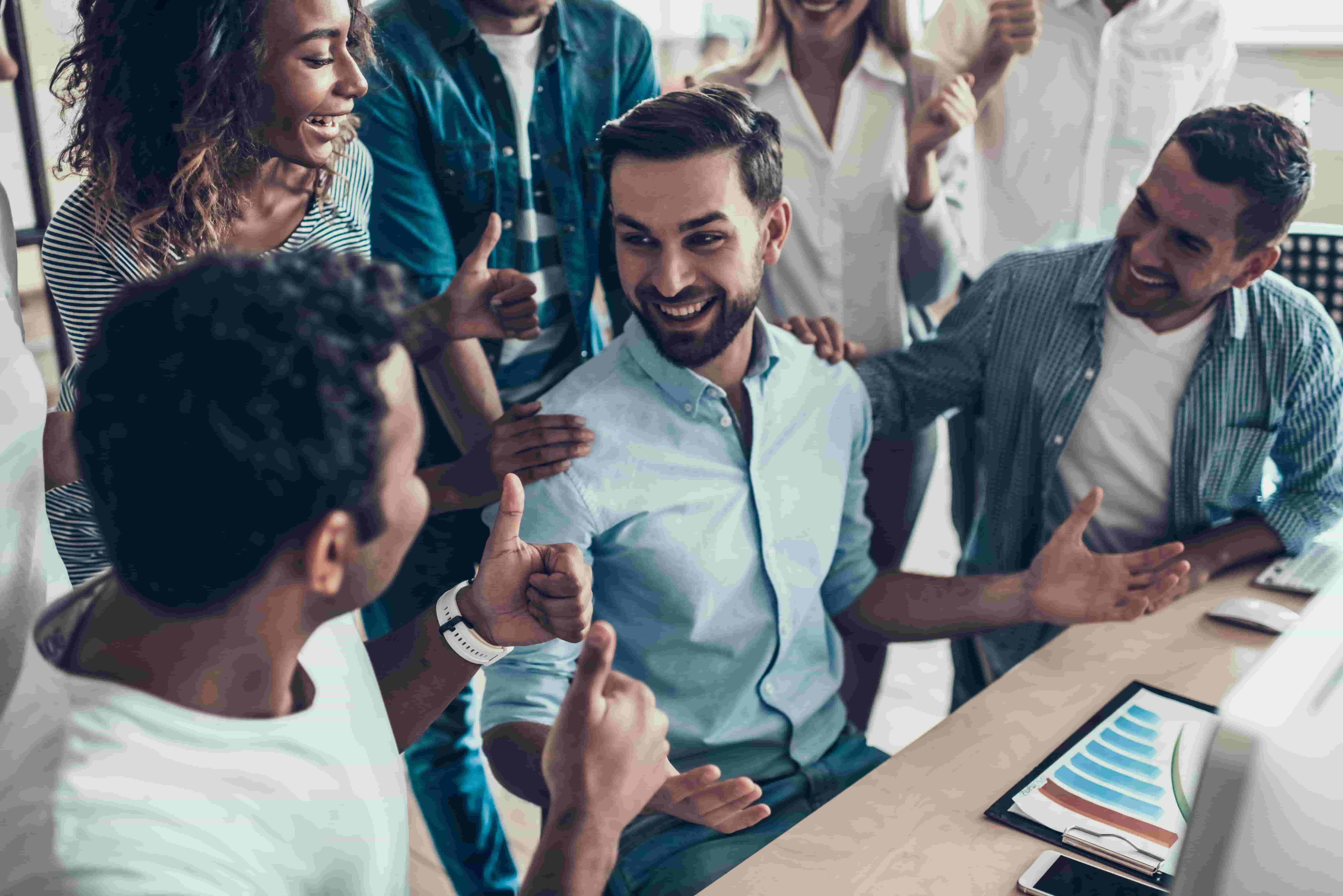 Busy worker is congratulated by his team for increasing profits